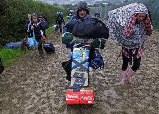 GLASTONBURY, ENGLAND - JUNE 22:  Music fans arrive in the mud and the rain at the Glastonbury Festival site at Worthy Farm, Pilton on June 22, 2011 in Glastonbury, England.  Heavy rain and mud greeted music fans as the gates to the five-day festival opened to the public this morning. This year the festival will feature headline acts U2, Coldplay and Beyonce. The festival, which started in 1970 when several hundred hippies paid 1 GBP to watch Marc Bolan, has grown into Europe's largest music festival attracting more than 175,000 people over five days.  (Photo by Matt Cardy/Getty Images)