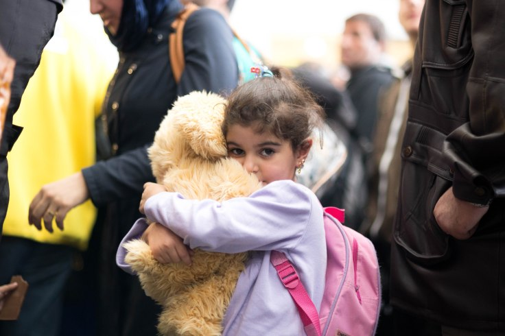 A young migrant girl hugs her newly gotten cuddly toy.