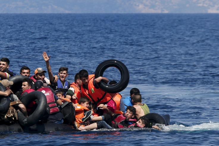 Syrian and Afghan refugees fall into the sea after their dinghy deflated some 100m away before reaching the Greek island of Lesbos, September 13, 2015. Of the record total of 432,761 refugees and migrants making the perilous journey across the Mediterranean to Europe so far this year, an estimated 309,000 people had arrived by sea in Greece, the International Organization for Migration (IMO) said on Friday. About half of those crossing the Mediterranean are Syrians fleeing civil war, according to the United Nations refugee agency. REUTERS/Alkis Konstantinidis TPX IMAGES OF THE DAY - RTSUQ8